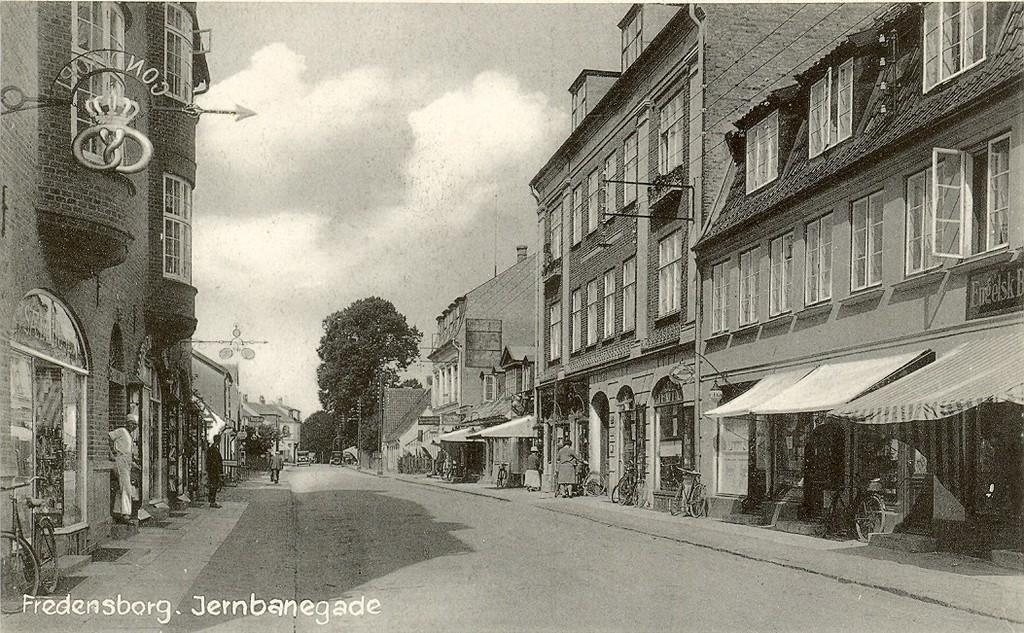 3480.14  Jernbanegade 26 bygget år 1915 til venstre med sæbehuset. Dernæst Baggesminde nr. 24. Arnstrupejendommen nr. 24 A er endnu ikke bygget, så kortet er fra efter 1915, men før 1932 hvor nummer 24 A blev bygget.