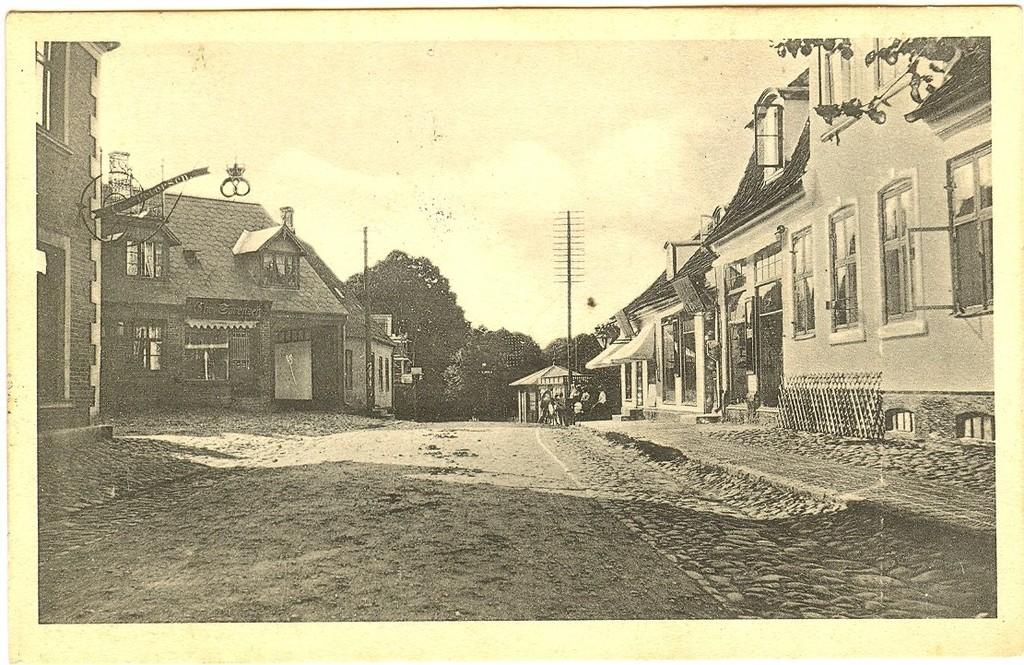 3480.15  Jernbanegade med bager Chr. Christensens ejendom (senere Ravnbaks) til venstre. Dernæst Chr. Sørensens ejendom Jernbanegade 14, bygget 1909. Senere ombygget 1934 for Slagtermester V. Jørgensen 1934 til den form vi kendte da slagtermester Svend Jørgensen havde ejendommen. Købmandsgården til højre og bagerst til højre Acaciabygningen hvor der solgtes blomster, grønt og meget andet. Kortet er poststemplet i 1915.