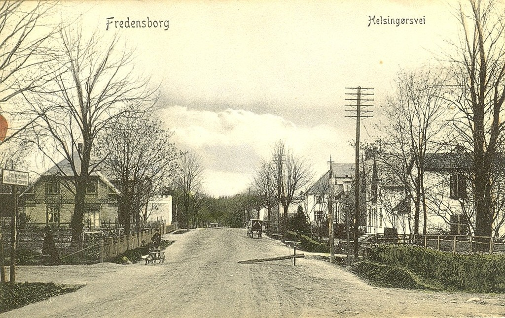 3480.16  Helsingørsvej nummer 9 til venstre hvor Købmand Mønsted havde forretning og hvor Jellum senre startede sin farvehandel. Senere flyttede Jellum til Jernbanegade og Georg Nielsen overtog forretningen. Forretningen er bygget ca. 1908-10. Der er billeder fra Fredensborghus hvor købmandsforretningen overfor endnu ikke er bygget. Den store hvide bygning med tegltag Fredensborghus blev bygget i 1901.  Hvad brugtes de pudsige bjælker i vejsiderne til ? Var det datidens fartbegrænsning ?