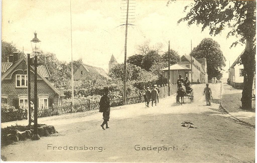 3480.34  Starten af Jernbanegade ved Slotsgade i september 1906. Vandtårnet i baggrunden var netop indviet i april samme år og Jernbanegade 6 der ligger skjult bag træet til højre blev opført 1905. Nummer 10 og 12 er endnu kun små lave beboelseshuse.  Købmandsgården, Jernbanegade 3 ses til venstre for de to damer med lyse hatte.