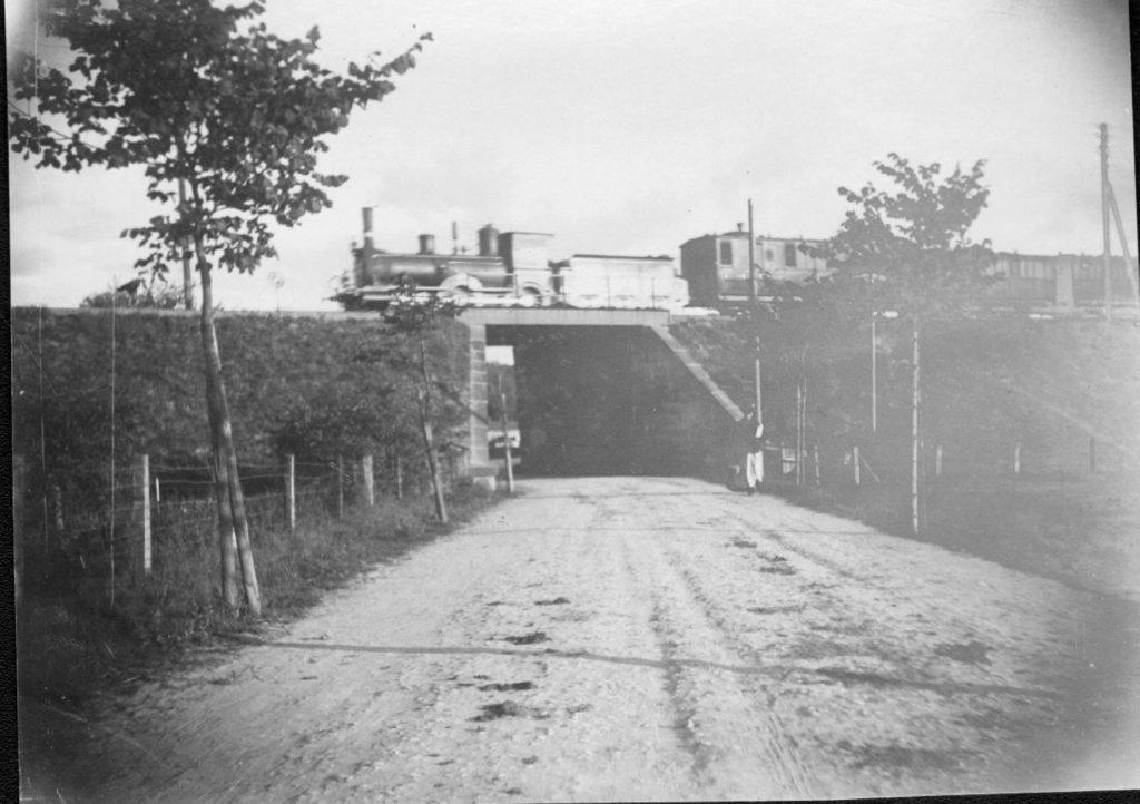 """10578.7 Jernbanebroen ved Hammersholtvej i Hillerød. Billedet er fra før 1930 hvor den nye bro (den nuværende ) blev bygget. DSB ville betale for en 8m bred viadukt, sognerådet forlangte 10m og med tilskud fra den statslige togfond endte man med 11 m. Kilde : """" Nordbanen"""" ved John Poulsen. Damplokomotivet er et litra DS  FB Hillerød 28.11.2016"""