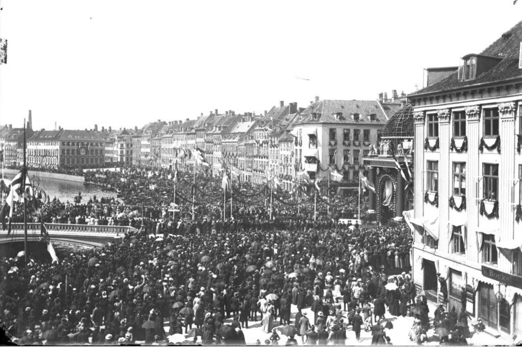 10972.18 Billede fra Christian IX guldbryllup i 1892, d. 26 maj. Menneskemængden kigger på kareterne, som kører over Højbro, til portalen som er opstillet i anledning af guldbrylluppet, der hvor statuen af Biskop Absalon i dag står. G.K. 23.5.2018   1200 K