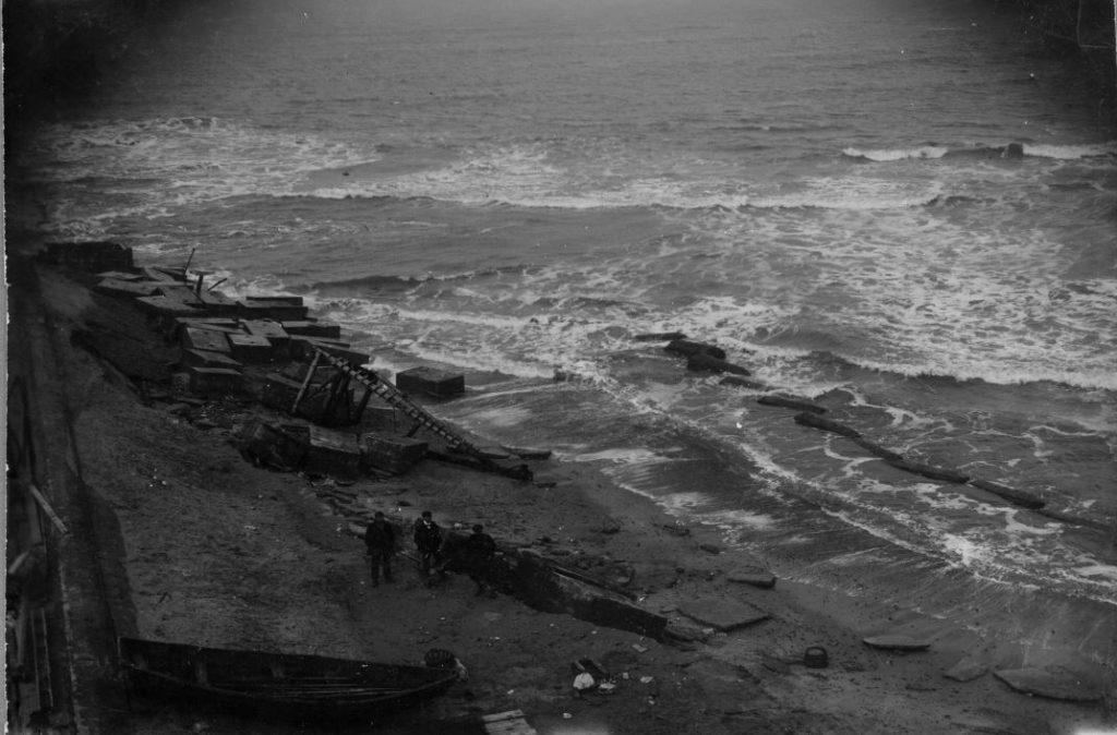 """71.125  Vorupør 4 februar 1909. """" Terrainet mellem dæmningen og Østre Høfd taget dagen efter stormen 4 februar 1909. ½ fod lavvande. Man ser dønningerne endnu. Bygningerne blev revet ned """" 7700  FB Vorupør 9.9.2017"""