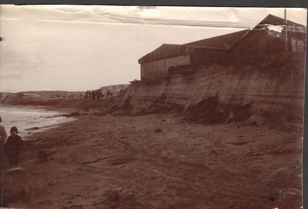 """71.128 Vorupør 4 februar 1909. """" Man ser den lodrette brink med dens mange rallag, det tidligere fundament for cementskuret ragede udover brinken. Cementskuret flyttedes tilbage i december 1908. Fiskerkompagniets pakhus står for fald og VBV´s arbejde med brinken udfor bådepladsen. ( øverste del 8 alen tilh. Fiskehandler Munk Madsen flyttet i januar 1909"""" 7700"""