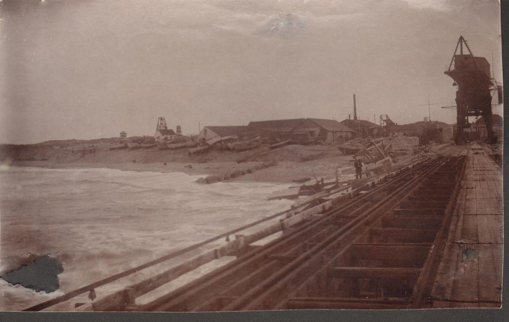 """71.129 Vorupør november 1908. """" billede af bådepladsen og dæmningen, taget fra broen den 20. november 1908 i ret solrigt, men mørkt vejr. Ingeniør Sletting, Sct. Nikolajvej 15, Kbh. V. Vi måtte jævne skrænterne ud for at fiskerne overhovedet kunne komme frem på havet med deres både."""" 7700"""