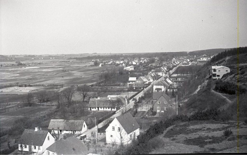 """100.5.12 Udsigt over Strandvejen. Huset til højre er """"lægeboligen"""" nummer 45. Det hvide hus i to plan forrest i billedet er Stålvej 2."""